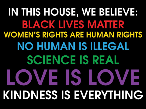"The signboard contains text supporting black lives. The text reads, ""in this house, we believe: black lives matter, women's rights are human rights, no human is illegal, science is real, love is love, kindness is everything."" The image background is black"
